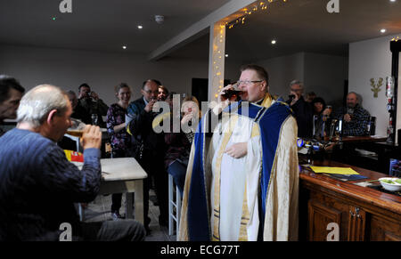 Brighton UK 12th December 2014 - Local Moulsecoomb vicar Father John Hall blesses the newly refurbished Bevy pub - Stock Photo