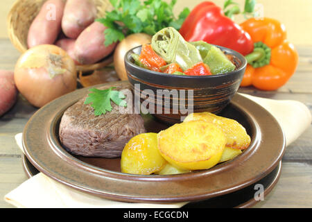 ostrich steak with baked potatoes and mediterranean vegetables - Stock Photo