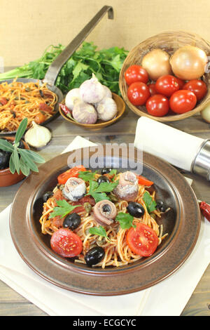 a plate of pasta, olives, tomatoes, anchovies and capers - Stock Photo