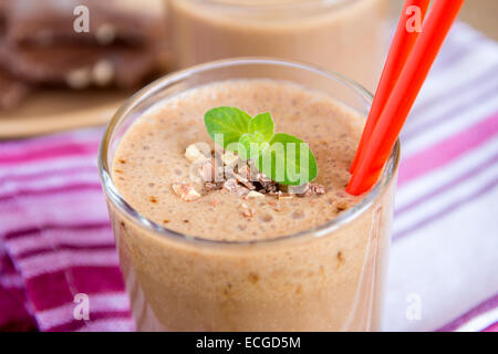 Milkshake (chocolate and banana smoothie) in glass with mint and nuts, homemade dairy breakfast horizontal close - Stock Photo