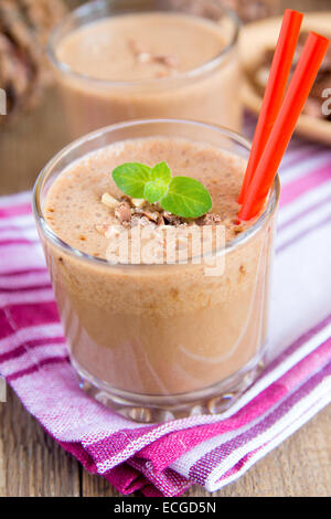 Milkshake (chocolate and banana smoothie) in glass with mint and nuts, homemade dairy breakfast or dessert vertical - Stock Photo