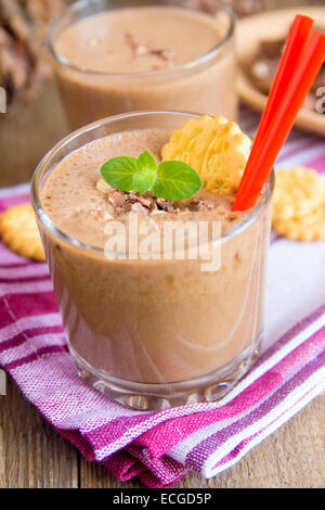 Milkshake (chocolate and banana smoothie) in glass with mint, cookies and nuts, homemade dairy breakfast or dessert - Stock Photo