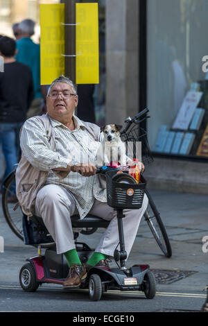 A man on a disability scooter with small dog on his lap in Oxford, England - Stock Photo