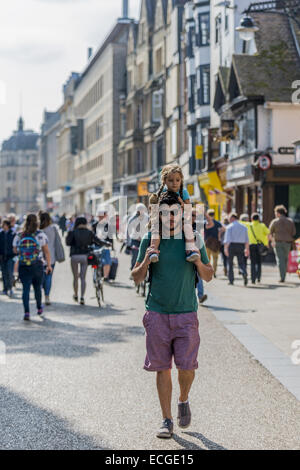 Man walking down the street wearing sunglasses and shorts, with his daughter on his shoulders carrying a teddy bear, - Stock Photo