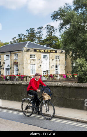 A man cycles over Folly Bridge on the Abingdon Road in Oxford with the famous pub The Head of the River behind him - Stock Photo
