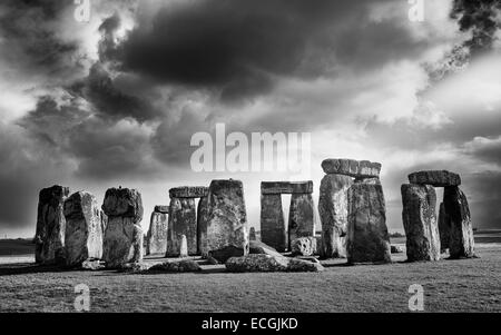 Stonehenge, prehistoric monument, set against a foreboding sky and a blue sunny at Amesbury, Wiltshire, UK. - Stock Photo