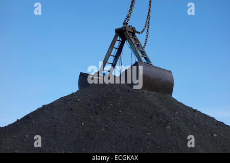 The top of a huge coal pile with clamshell bucket - Stock Photo