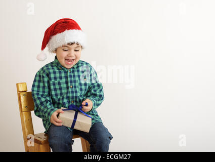 happy boy in a cap of Santa Claus opens Christmas gift - Stock Photo