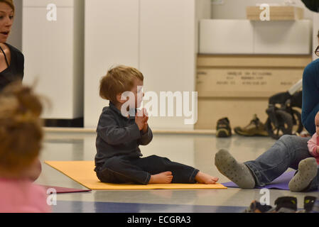 Infants doing yoga in daycare - Stock Photo