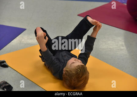 Infant doing yoga in daycare - Stock Photo