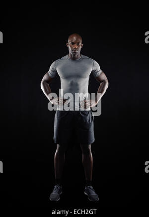 Full length portrait of muscular young man in sportswear looking at camera against black background. Strong African - Stock Photo