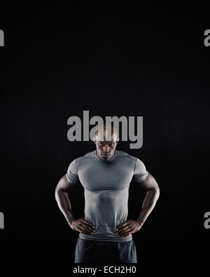 Portrait of muscular young man in sportswear staring at camera against black background. African athlete with his - Stock Photo