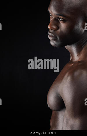 Cropped shot of a man standing shirtless in the studio. African male model with muscular build on black background - Stock Photo