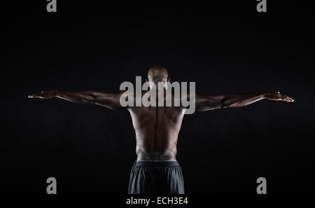 Portrait of a strong back of a African muscular man stretching his arms against black background. Rear view of fitness - Stock Photo