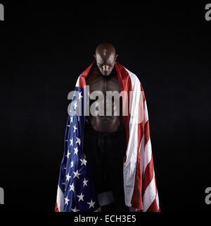 Male athlete carrying an American flag against black background. Studio shot of muscular sportsman with USA flag. - Stock Photo