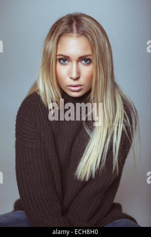 Portrait of beautiful young blond woman in sweater looking at camera. Caucasian female model against white wall. - Stock Photo