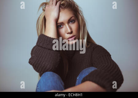 Image of beautiful female model wearing sweater with her hand in hair. Studio shot of attractive woman. - Stock Photo