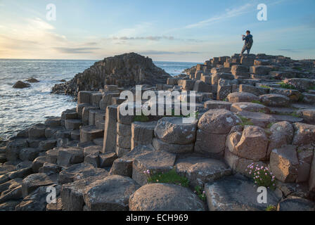 Photographer at the Giant's Causeway, Causeway Coast, County Antrim, Northern Ireland. - Stock Photo