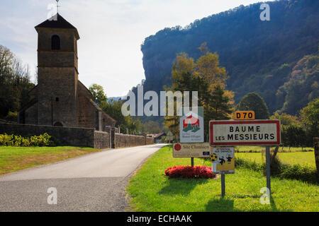 Village sign and church below escarpment in Jura mountains on D70 road. Baume-les-Messieurs, Jura, Franche-Comte, - Stock Photo