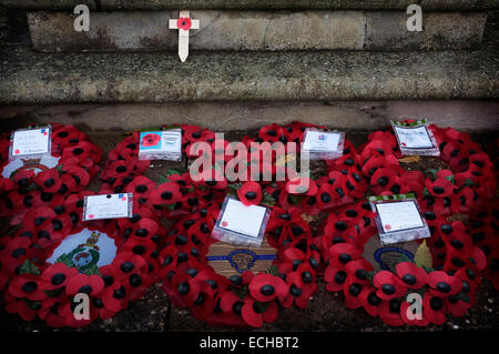 Poppy appeal wreaths laid in front of a war memorial, one wooden cross poppy rests on the memorial. - Stock Photo