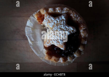 Half eaten mince pie with icing dusted star. - Stock Photo