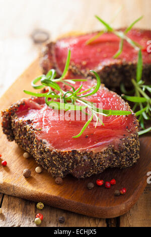 raw beef steak with spices and rosemary on wooden background - Stock Photo