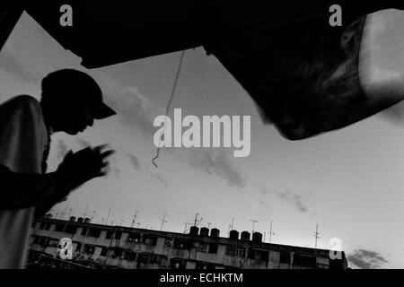 Yuri C., a Cuban hip-hop fan and musician, smokes a cigarette on the balcony in the apartment block of Alamar, a - Stock Photo