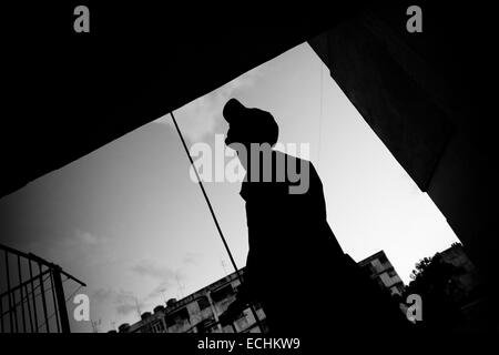 Jorge D., a Cuban hip-hop fan, walks out of the large apartment block of Alamar, a large public housing complex - Stock Photo