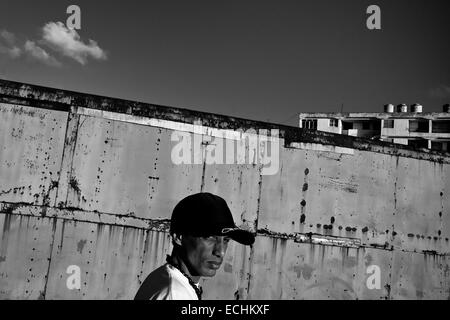 Yuri C., a Cuban hip-hop fan and musician, poses for a picture in front of the apartment block in Alamar, a large - Stock Photo