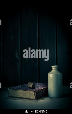 Uncorked earthenware bottle and old leather bound book. - Stock Photo
