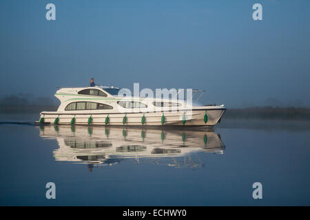 Reflection of a cruise boat crossing Lough Ree, River Shannon, County Westmeath, Ireland. - Stock Photo