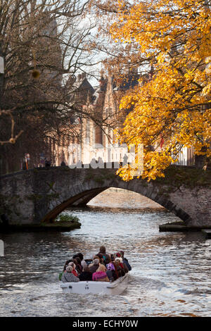 Tourists on a boat trip on the canals in autumn; Bruges, Belgium, Europe - Stock Photo