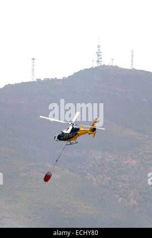 Firefighting helicopter extinguishing fire - Stock Photo