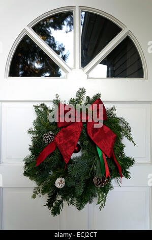Homemade traditional green and red Christmas wreath hanging on the white front door of a house - Stock Photo
