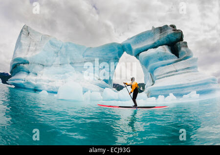 One man on stand up paddle board (SUP) paddles past hole melted in iceberg on Bear Lake in Kenai Fjords National - Stock Photo