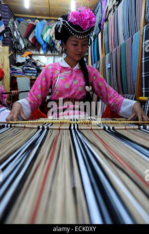 China, Yunnan Province, Lijiang, old town listed as World Heritage by UNESCO, weaver in one of the many stalls - Stock Photo