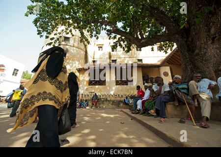 Kenya, Lamu archipelago, Lamu, Woman fully black covered walking by the Lamu Fort - Stock Photo