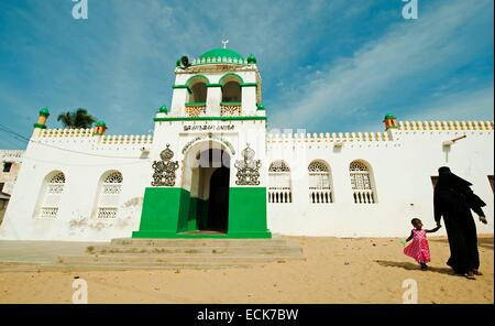 Kenya, Lamu archipelago, Lamu, veiled woman walking with child in front of mosque - Stock Photo