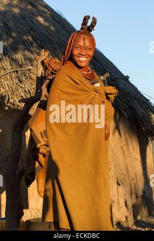 Namibia, Kunene region, Kaokoland, Himba village near Opuwo, Himba woman in front of a hut - Stock Photo
