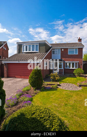 Vertical exterior of a typical 1980's detached house in the sunshine. - Stock Photo