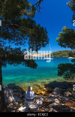 Croatia, Dalmatia, National park of Kornati, Dugi Otok, retired couple sitting on the bank, in the shade of pine - Stock Photo