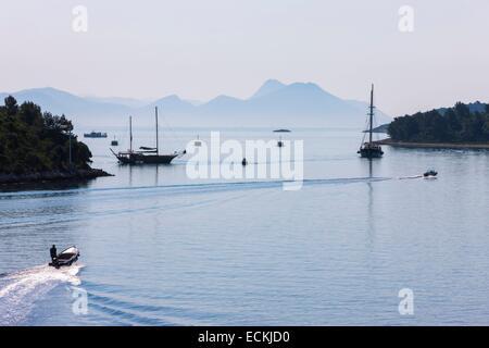 Croatia, Dalmatia, Dalmatian coast, Korcula Island, Korcula, motorboat across a bay or other sailboats anchored - Stock Photo