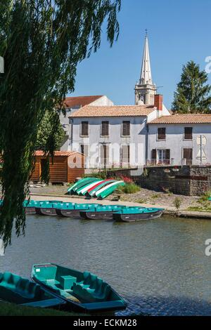 France, Vendee, Damvix, Marais Poitevin, boats on the Sevre Niortaise river and the bell tower - Stock Photo