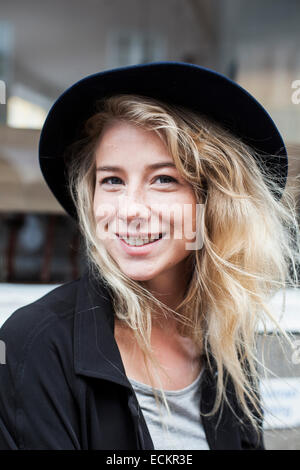 Portrait of happy young woman wearing hat - Stock Photo