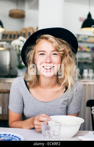 Portrait of happy young woman in restaurant - Stock Photo