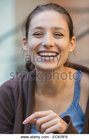 Portrait of young woman laughing outdoors - Stock Photo