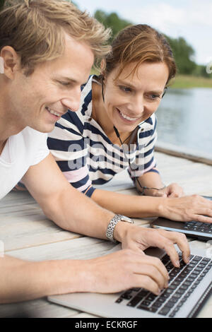 Happy mature woman with man using laptop on pier - Stock Photo