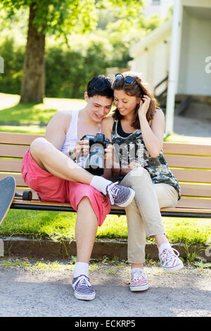 Happy couple looking photos on camera while sitting on bench in park - Stock Photo