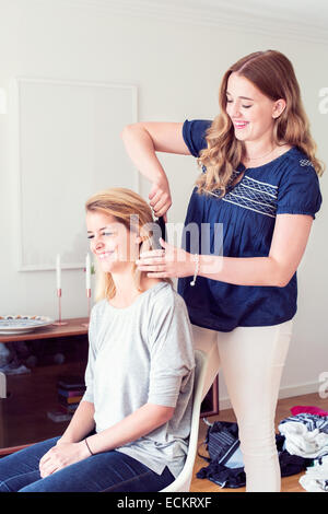Young woman brushing sister's hair at home - Stock Photo