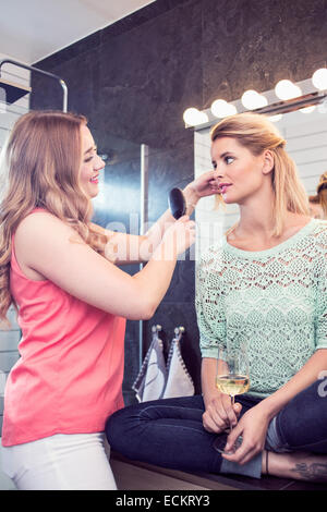 Young woman brushing sister's hair in bathroom - Stock Photo